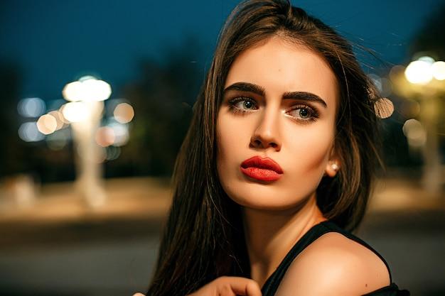 Superbe jeune mannequin en regardant la caméra pose dans la ville, vêtue d'une robe de soirée noire.