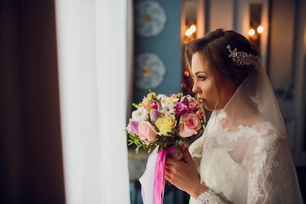 Superbe jeune mariée tenant le bouquet