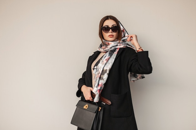 Superbe jolie jeune femme professionnelle en lunettes de soleil élégantes en manteau noir tendance avec sac en cuir avec un foulard vintage sur la tête posant près d'un mur à l'extérieur. mannequin de jolie fille. dame sexy