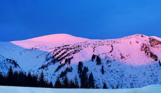 Superbe lever de soleil dans les montagnes avec des pics enneigés une vue panoramique sur le couvert de givre