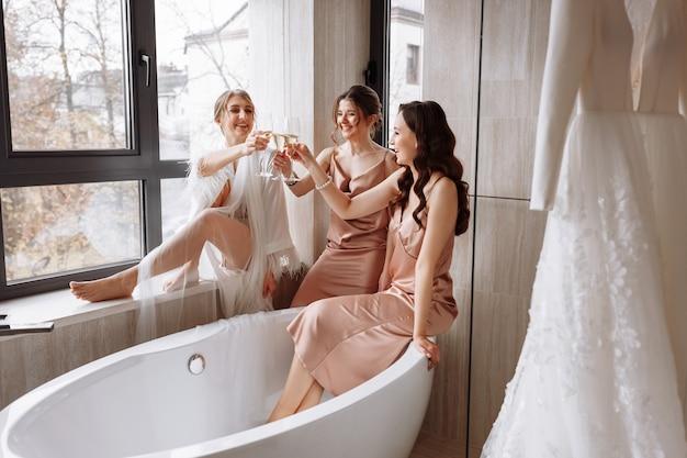 Superbe mariée avec les meilleures demoiselles d'honneur tiennent des verres et boivent du champagne dans la salle de bain de l'hôtel près de la fenêtre