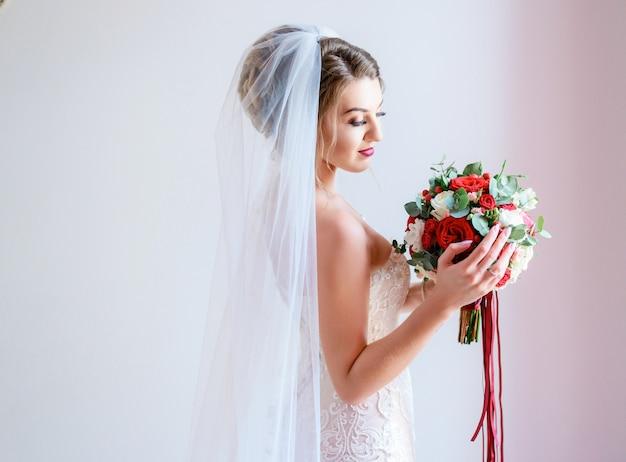 Superbe mariée en robe chic pose avec un bouquet de roses rouges et de pivoines