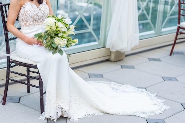 Superbe mariée avec une robe de mariée de luxe assis sur une chaise tenant un bouquet de mariée