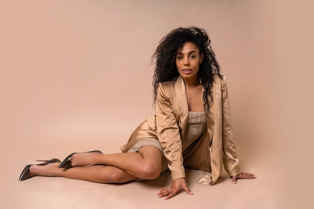 Superbe modèle bronzé avec une coiffure frisée volumineuse en robe dorée brillante et un blazer en satin assis.