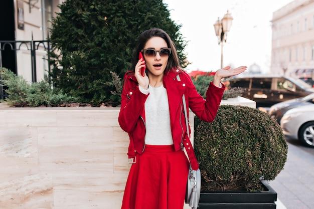 Superbe modèle féminin en lunettes de soleil marron appelant quelqu'un, debout dans la rue