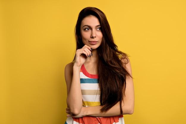 Superbe modèle féminin posant avec l'expression du visage. portrait de gros plan de l'élégante fille européenne debout avec un regard ludique devant le mur