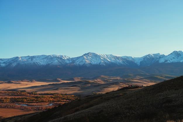 Superbe paysage d'automne avec la foule de touristes sur la colline avec vue sur la vallée rouge et la grande chaîne de montagnes enneigée au soleil rouge du coucher du soleil. vue ensoleillée spectaculaire sur les montagnes enneigées et la vallée d'automne.
