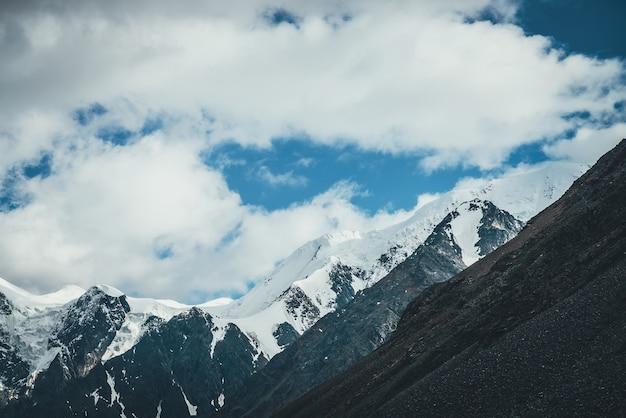Superbe paysage de montagne avec un grand sommet enneigé. paysages atmosphériques avec une haute montagne blanche comme neige avec glacier. grandes montagnes avec de la neige. vue panoramique sur les rochers noirs géants avec de la neige blanche.