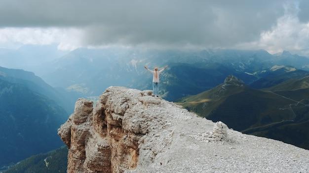 Superbe paysage de rochers de montagne et femme debout sur le dessus avec les bras tendus