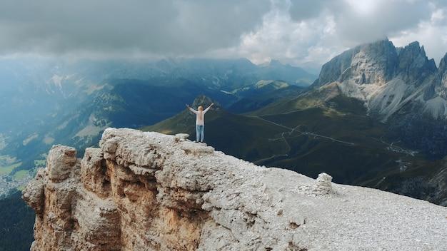 Superbe Paysage De Rochers De Montagne Et Femme Debout Sur Le Dessus Avec Les Bras Tendus Photo Premium