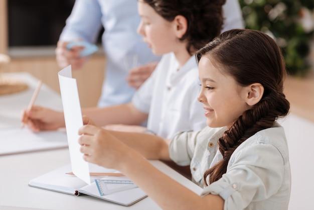 Superbe petite fille assise au comptoir de la cuisine, tenant une feuille de papier et essayant de lire pendant que son père et son frère font des sommes derrière
