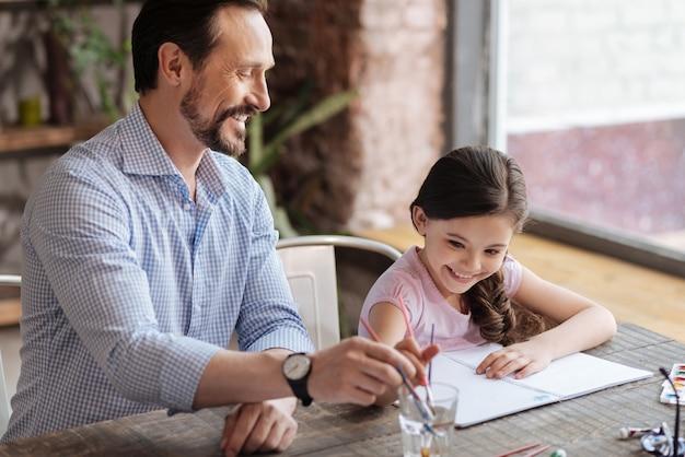Superbe petite fille joyeuse et son jeune père assis à la table et lavant leurs pinceaux dans un verre d'eau.