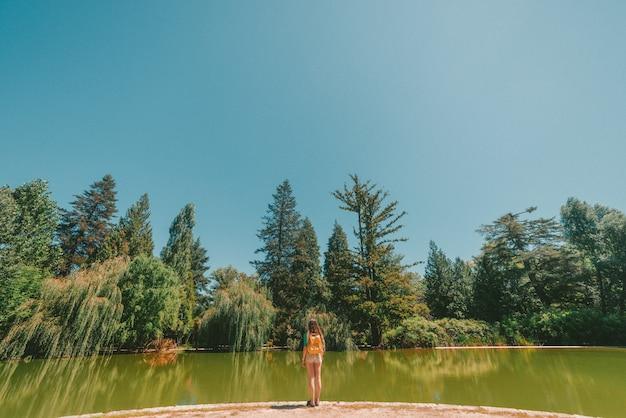 Superbe photo d'une femme debout devant une rivière au milieu d'une forêt par une chaude journée