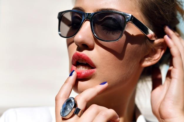 Superbe portrait de femme sensuelle, portant des lunettes de soleil argentées