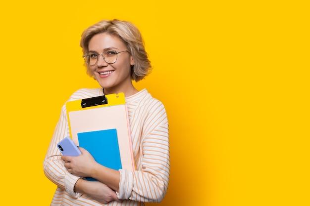 Superbe professeur blonde regardant à travers des lunettes tout en tenant des livres et posant sur un mur jaune avec espace libre