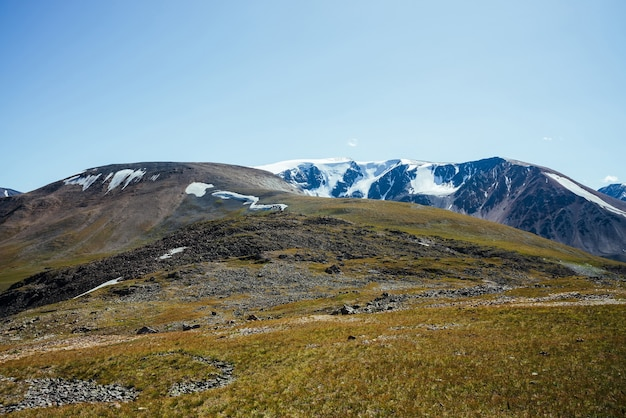 Superbe vue sur les grandes montagnes enneigées derrière la colline verte grand glacier sous le ciel bleu