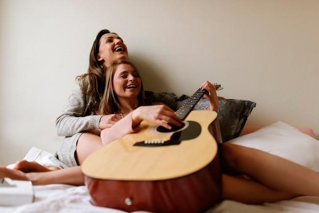 De superbes amis jouant de la guitare dans la chambre. concept de meilleur ami.