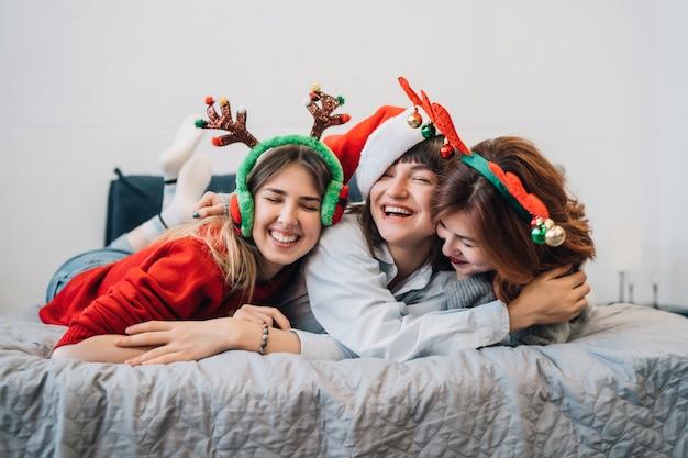 Superbes amis souriants s'amusant et profitant d'une soirée pyjama