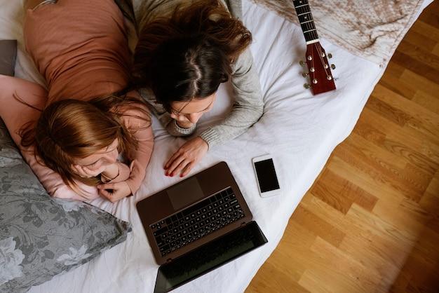 De superbes amis utilisant l'ordinateur portable dans la chambre. concept de meilleur ami.
