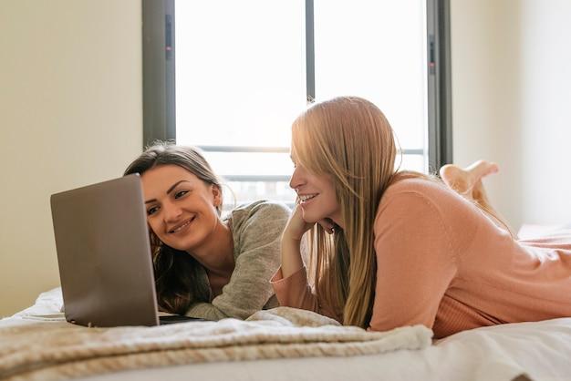 De superbes amis utilisant l'ordinateur portable dans la chambre. concept des meilleurs amis.