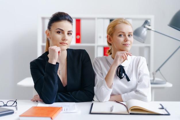 Superbes femmes assises ensemble sur le lieu de travail au bureau