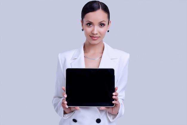 Superbes femmes latines en costume de mode blanc avec tablette numérique