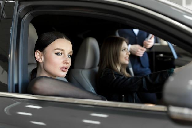 Superbes jeunes filles assises à l'intérieur de la voiture, souriant et regardant la caméra. une des filles se tenant la main sur le volant.