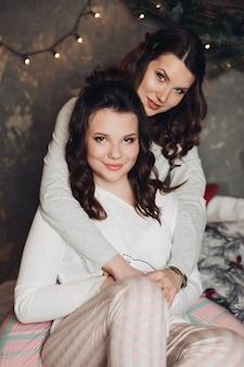 Superbes jeunes sœurs aux longs cheveux bruns en pyjama serrant contre la guirlande sur le mur derrière eux
