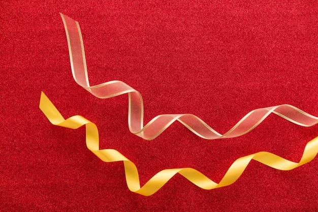 Superbes rubans dorés satinés brillants sur fond de papier glitter rouge coloré ou cadeau