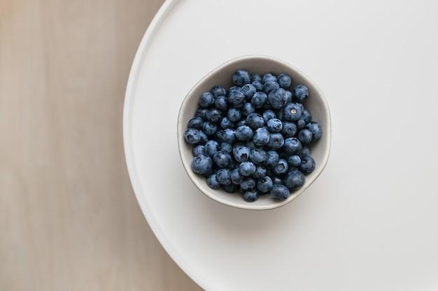 Superfood bio antioxydant aux myrtilles fraîches sur une table basse blanche, vue de dessus, concept de nutrition saine.