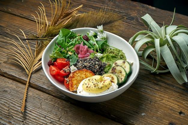Superfood - un bol de quinoa, fromage frit, guacamole, œuf poché poché et tomates cerises sur une table en bois