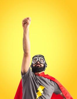 Superhero fait un geste de mouche sur fond coloré