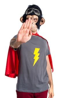 Superhero monkey man making stop sign