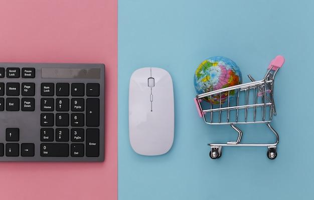 Supermarché mondial. clavier pc et caddie avec globe sur pastel bleu rose