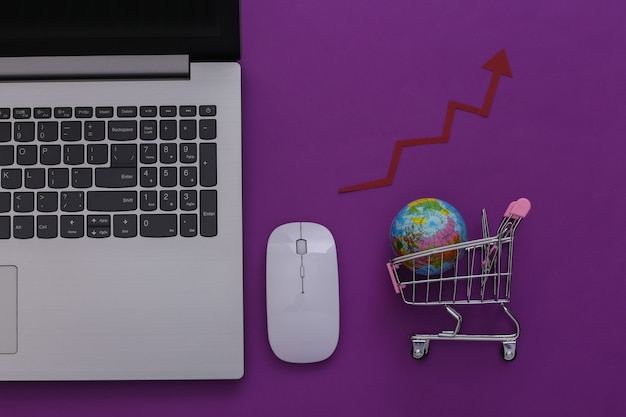 Supermarché mondial en ligne. ordinateur portable et mini caddie avec globe, flèche montante sur fond violet. vue de dessus. mise à plat