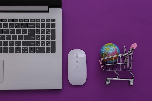Supermarché mondial en ligne. ordinateur portable et mini caddie avec globe sur fond violet. vue de dessus. mise à plat