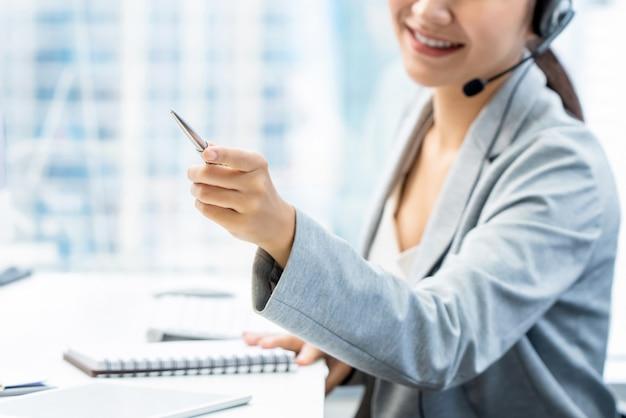 Superviseur du personnel de télémarketing femme pointant la main tout en travaillant au bureau