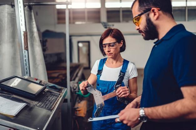 Superviseur féminin mesurant le produit découpé sur une machine à commande numérique