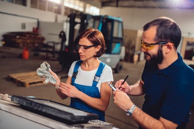 Superviseur féminin vérifiant l'ordre de travail de l'opérateur de la machine cnc
