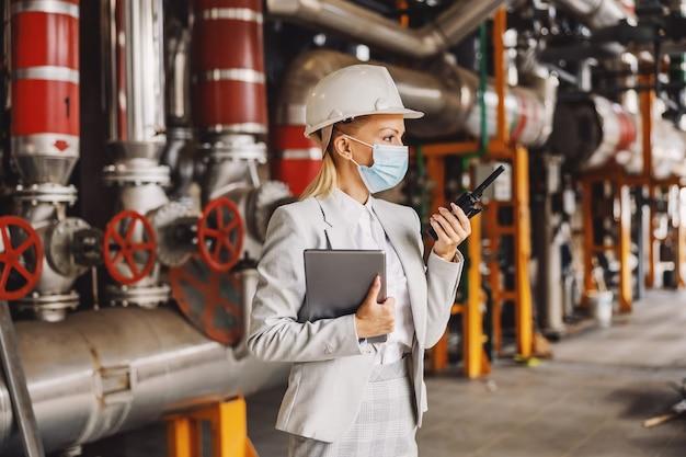 Superviseur holding tablet et parler au talkie-walkie en se tenant debout dans l'usine