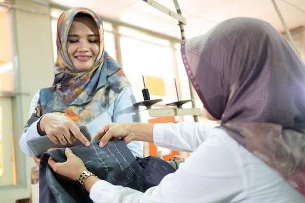 Superviseur musulman voilé avec un geste de la main pointé sur le tissu tenu par le tailleur