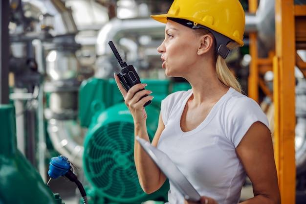 Superviseur tenant une tablette et parler au talkie-walkie en se tenant debout dans une installation de chauffage.