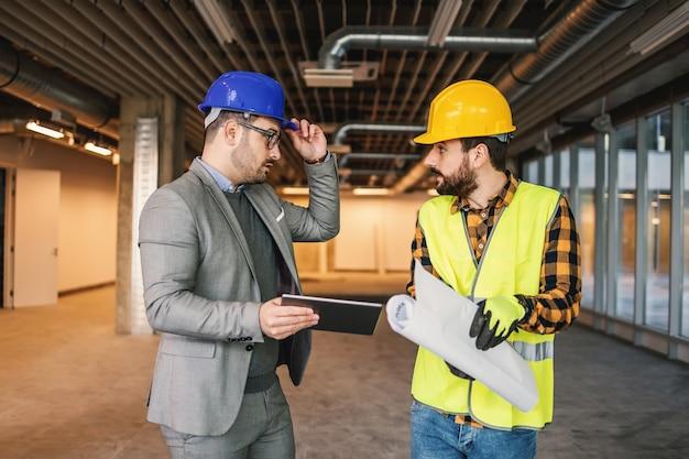 Superviseur et travailleur de la construction debout sur le chantier de construction et parler de projet.