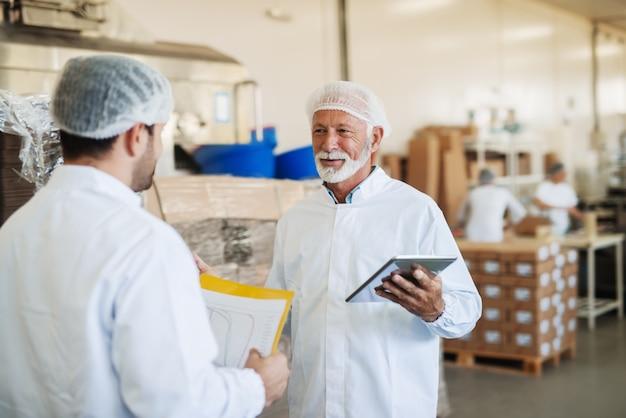 Les superviseurs parlent de la qualité des aliments. tableau des mains et tablette.