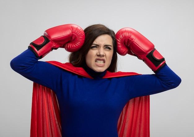 Superwoman agacé avec cape rouge portant des gants de boxe met les poings sur la tête isolé sur mur blanc