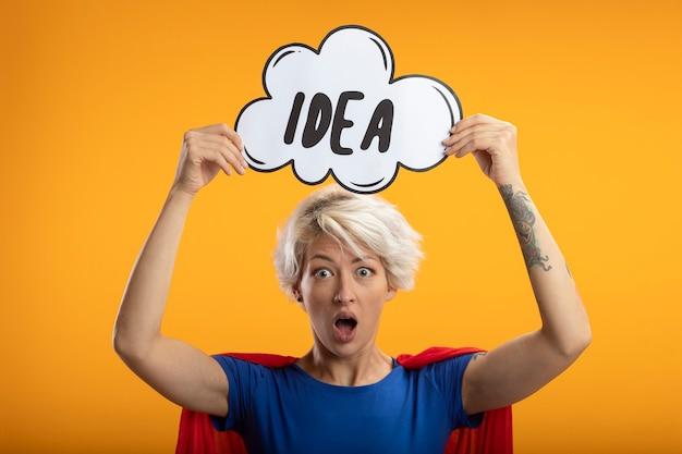 Superwoman anxieux avec cape rouge détient une bulle d'idée sur la tête isolée sur un mur orange