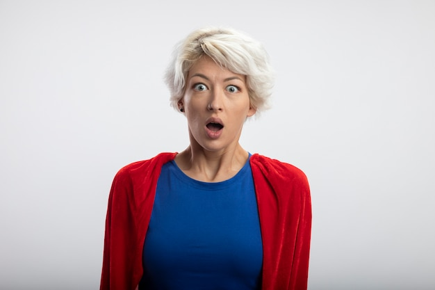 Superwoman choqué avec cape rouge regarde à l'avant isolé sur mur blanc