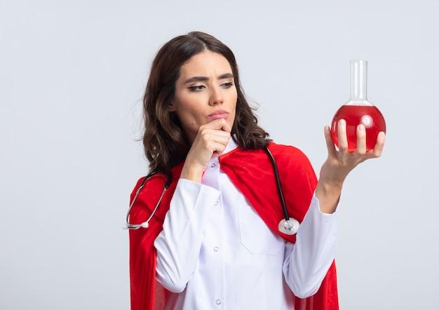 Superwoman confiant en uniforme de médecin avec cape rouge et stéthoscope met la main sur le menton et se penche sur un liquide chimique rouge dans un flacon de verre isolé sur un mur blanc