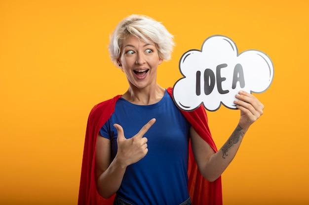 Superwoman excité avec cape rouge tient et pointe sur la bulle d'idée isolée sur le mur orange