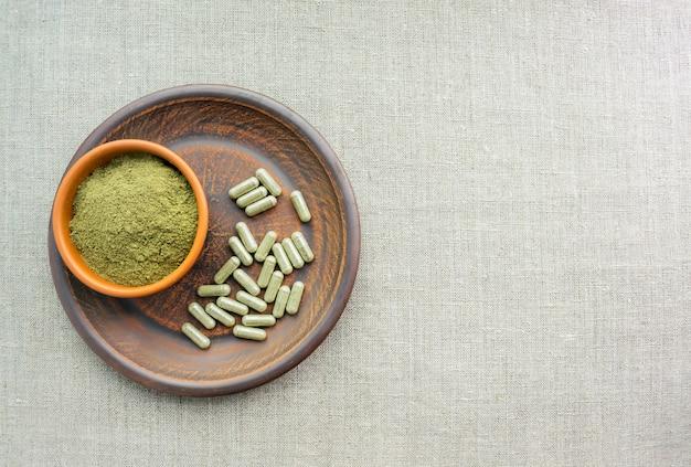 Supplément de capsules vertes de kratom et de poudre sur une plaque brune